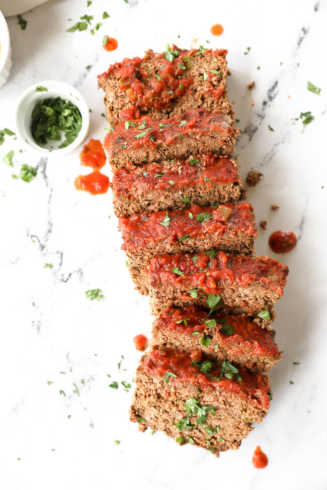Mexican taco meatloaf sliced and laid out with cilantro and salsa topping.