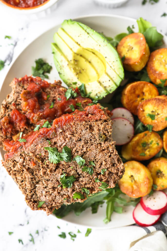 Mexican meatloaf slices on a plate with avocado, greens and sliced plantains close up vertical image