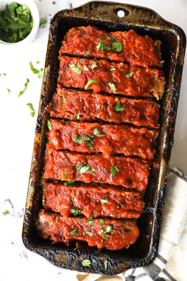 Taco meatloaf sliced in a pan with cilantro topping