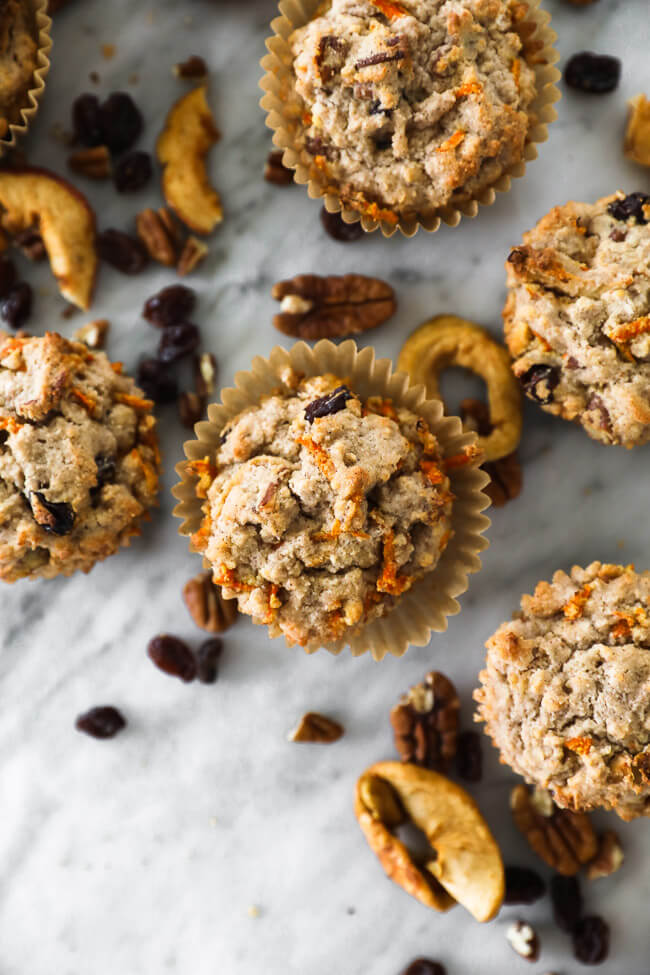 Vertical overhead close up of morning glory breakfast muffins on marble with pecans, dried and raisins sprinkled around.