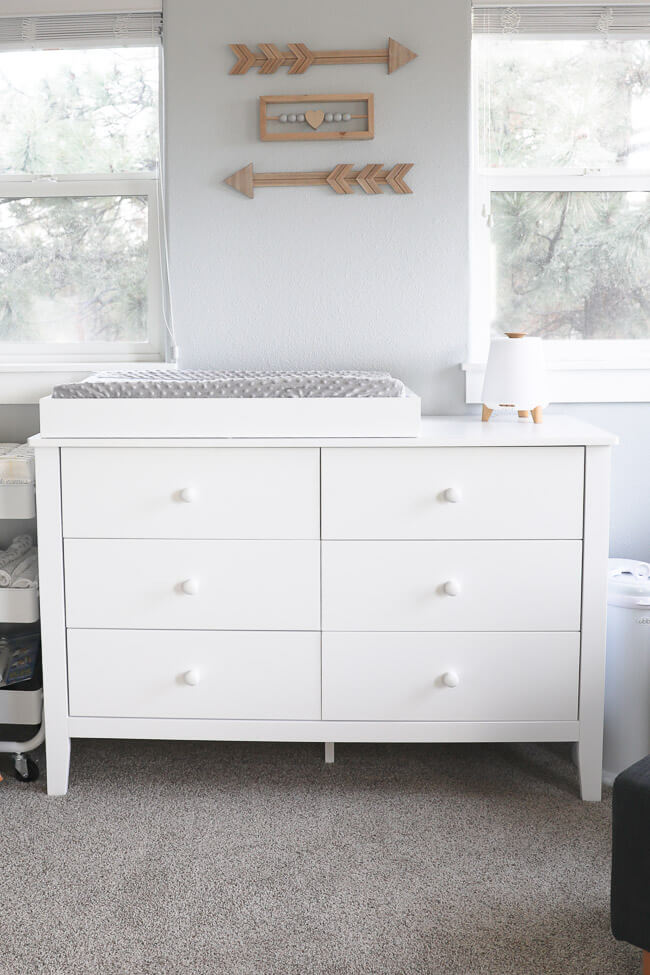 Vertical image of white dresser with chaining table topper and humidifier on top.
