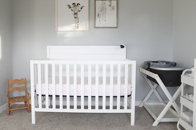 Horizontal image of white baby crib in nursery. Giraffe wall art above crib and bassinet and mini rocking chair off to the sides.
