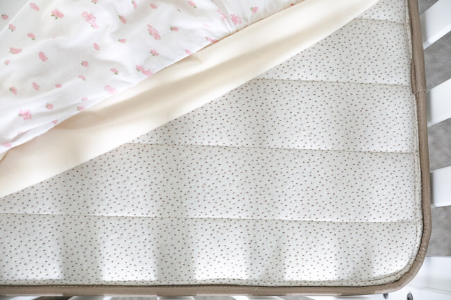 Horizontal overhead image of non-toxic crib mattress with waterproof mattress cover and fitted sheet pulled off the corner of the mattress.