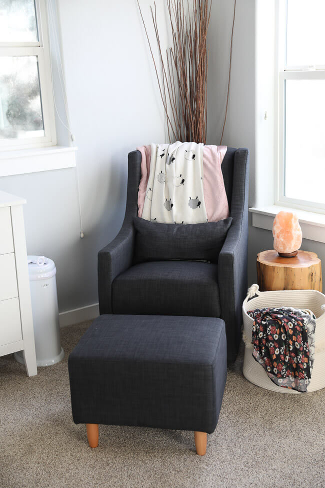 Vertical image of rocking chair/glider in baby room. Pink and sheet patterned blanket draped over the back of the chair with a side table and basket of more blankets to the side.
