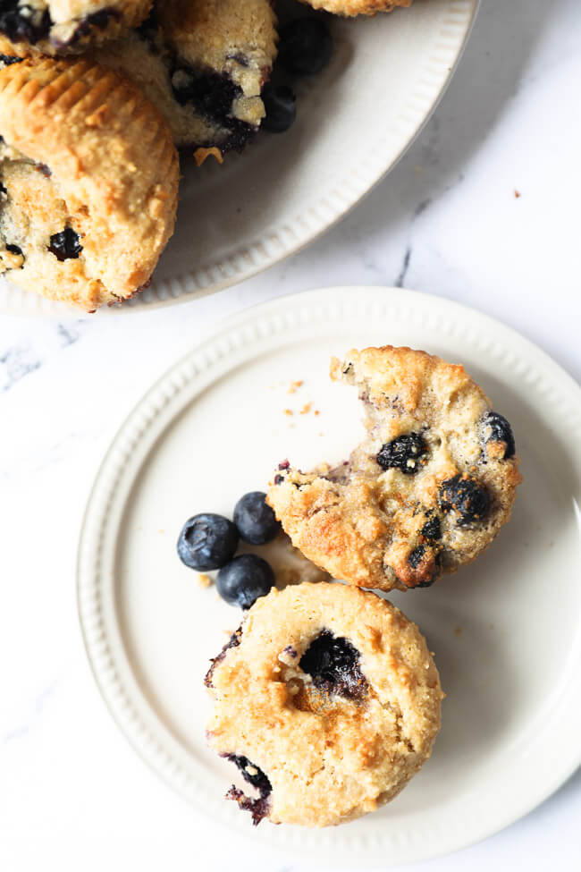 Vertical overhead image of a small plate with two gluten free blueberry muffins on it. One muffin has a bite taken out of it.