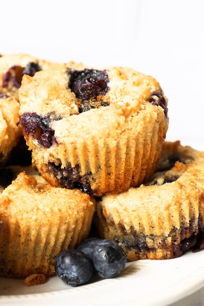 Close up straight on image of blueberry muffins stacked on a plate.