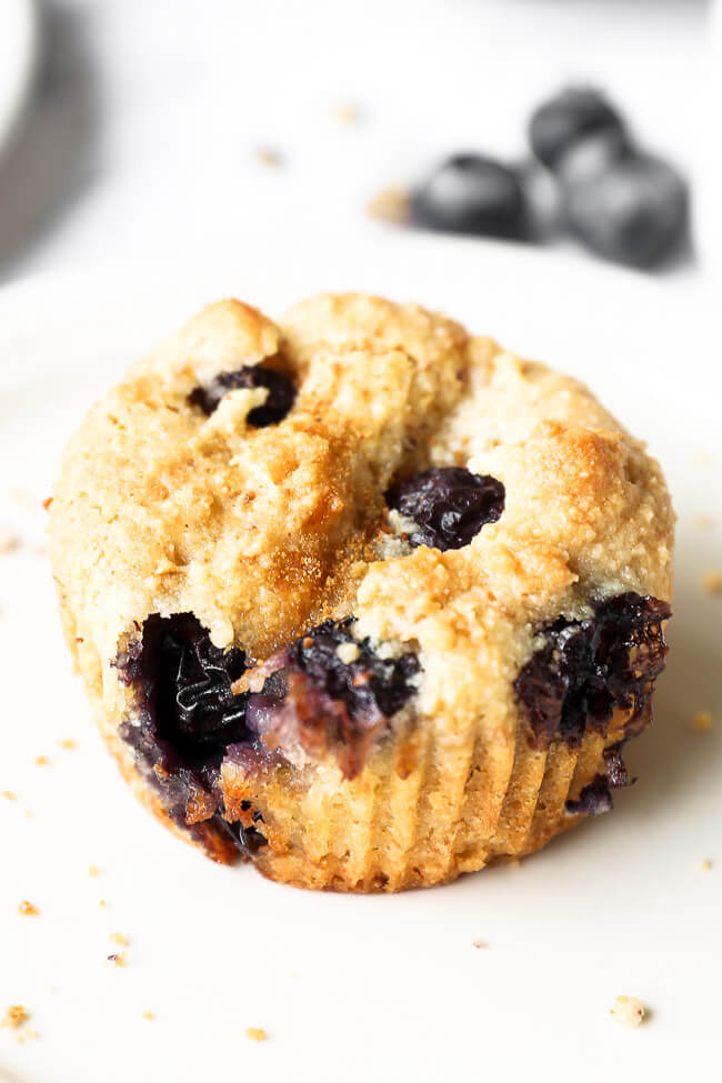 Close up angled image of one vegan blueberry muffin.