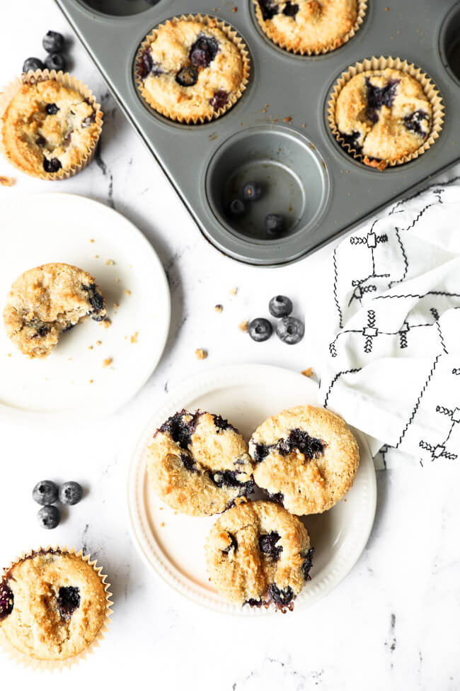 Vertical overhead image of muffins in tin and also on two small plates. One plate has one muffin with a bite taken out of it. The other plate has three muffins.