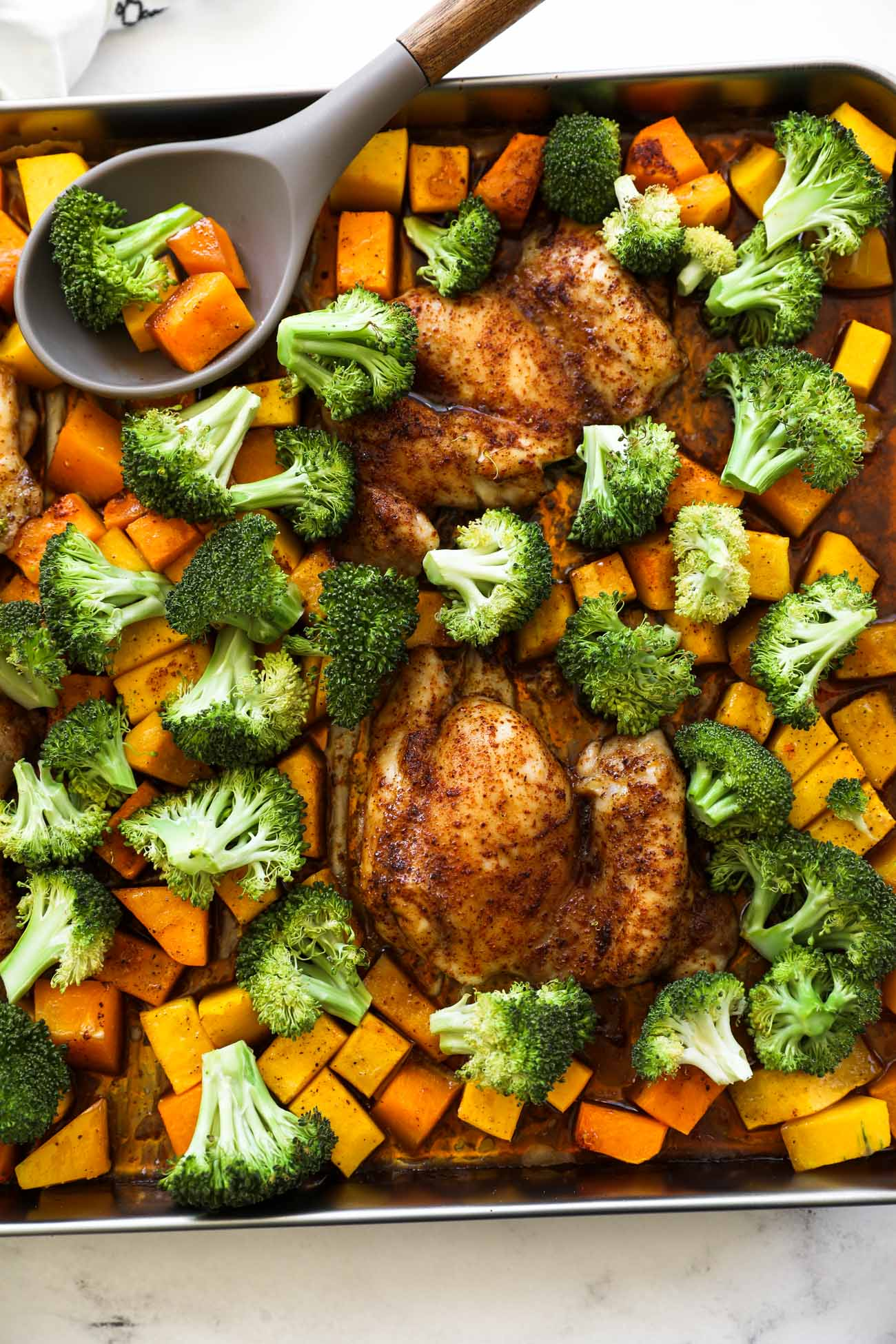 Overhead shot of one pan baked chicken and broccoli with squash pieces and a spoon in the pan