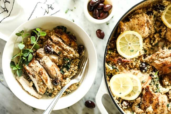 Horizontal image of one pan greek chicken dinner in skillet and served up in a bowl with a fork, with sprigs of fresh oregano on top.