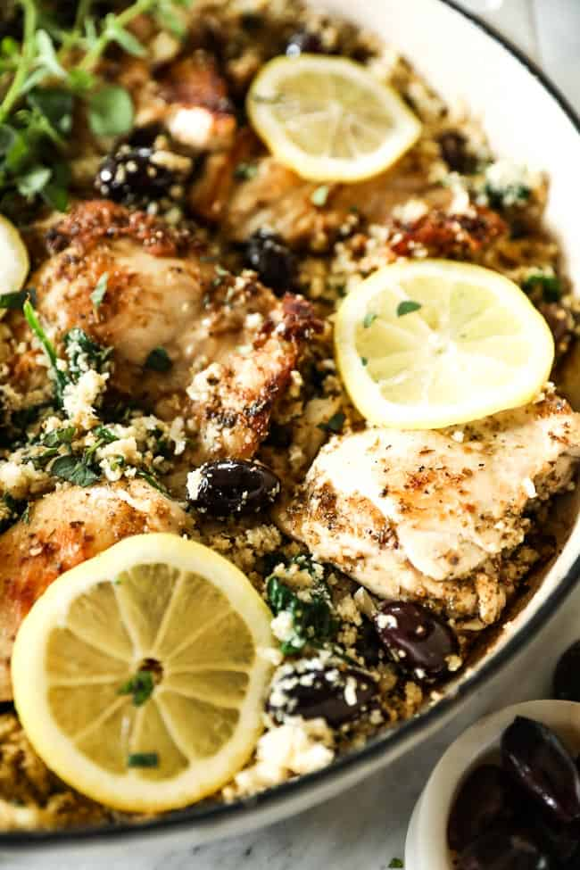 Close up vertical angled shot of greek chicken in a skillet with lemon slices on top.