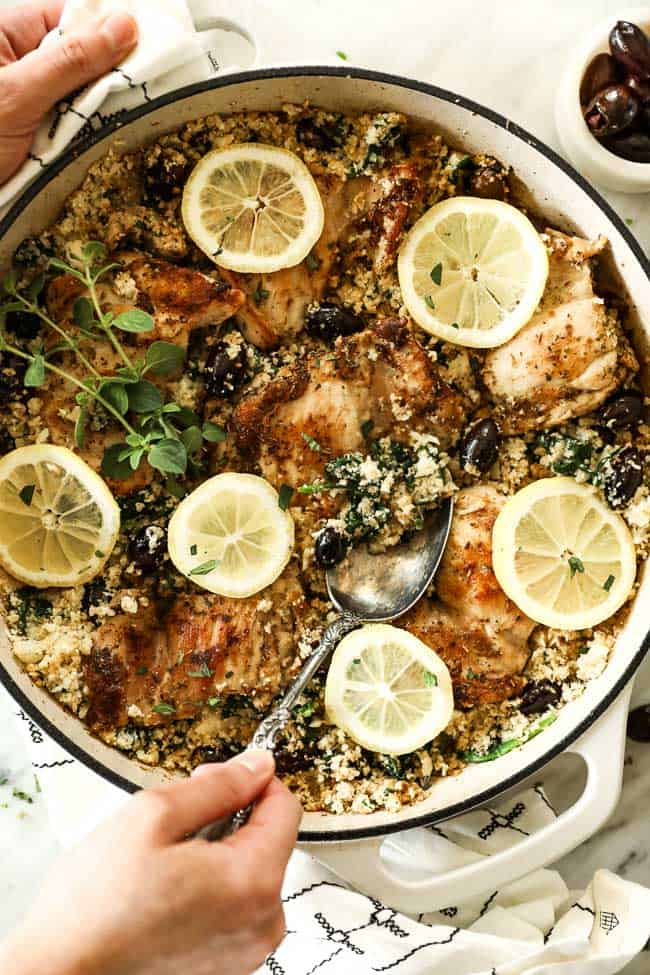 Vertical image of greek chicken in a skillet with a serving spoon. Topped with sliced lemon and fresh oregano.