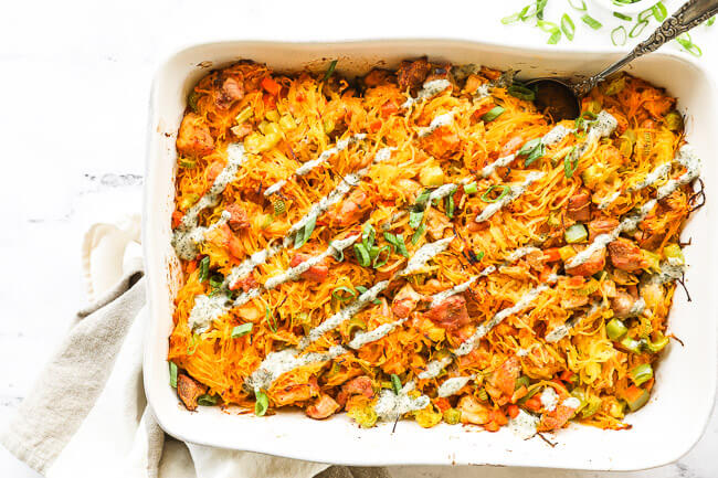 Overhead horizontal image of buffalo chicken casserole in casserole dish with chopped green onion and ranch drizzled on top and a serving spoon dug into dish.