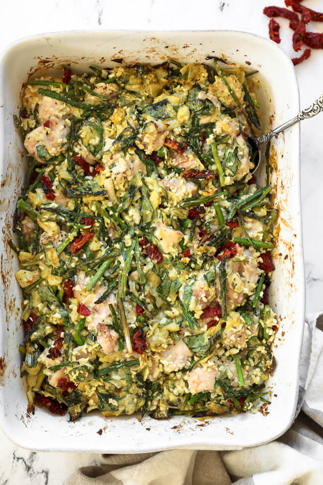 Creamy spinach artichoke chicken casserole in a casserole dish with a serving spoon dug in.