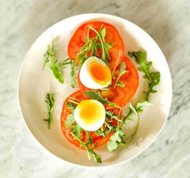 Sliced tomato topped with arugula and soft boiled egg on a plate