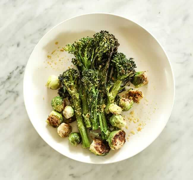 Roasted broccolini and brussels sprouts with nutritional yeast topping on a plate