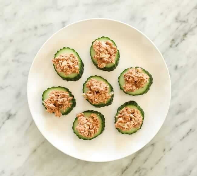 cucumber slices topped with tuna on a plate