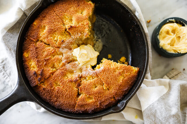 Paleo cornbread in a skillet with two pieces missing and whipped honey butter on top with more on the side.