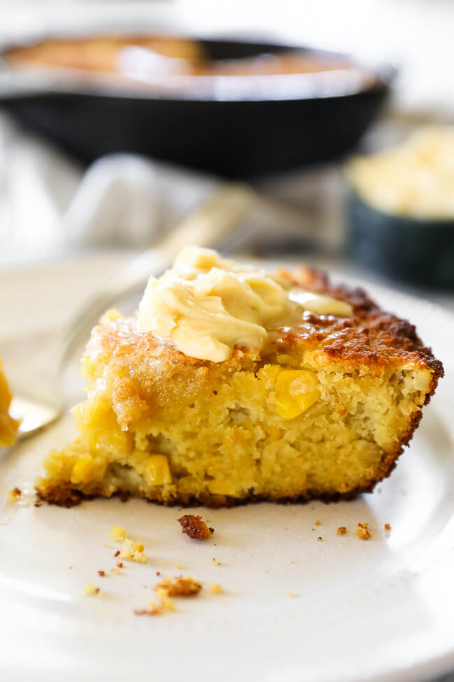 Angled image of a slice of paleo cornbread with whipped honey butter on top.