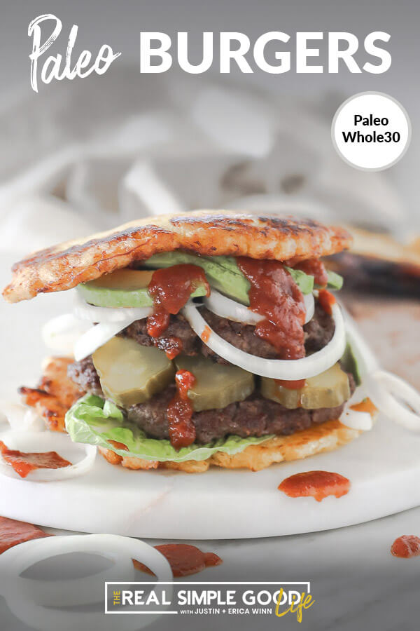 Paleo burger with plantain bun on board with avocado, onion pickle and ketchup dripping down. Close up straight on vertical image with text at top.