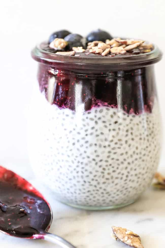Paleo chia seed pudding straight on shot of single jar with blueberry at top