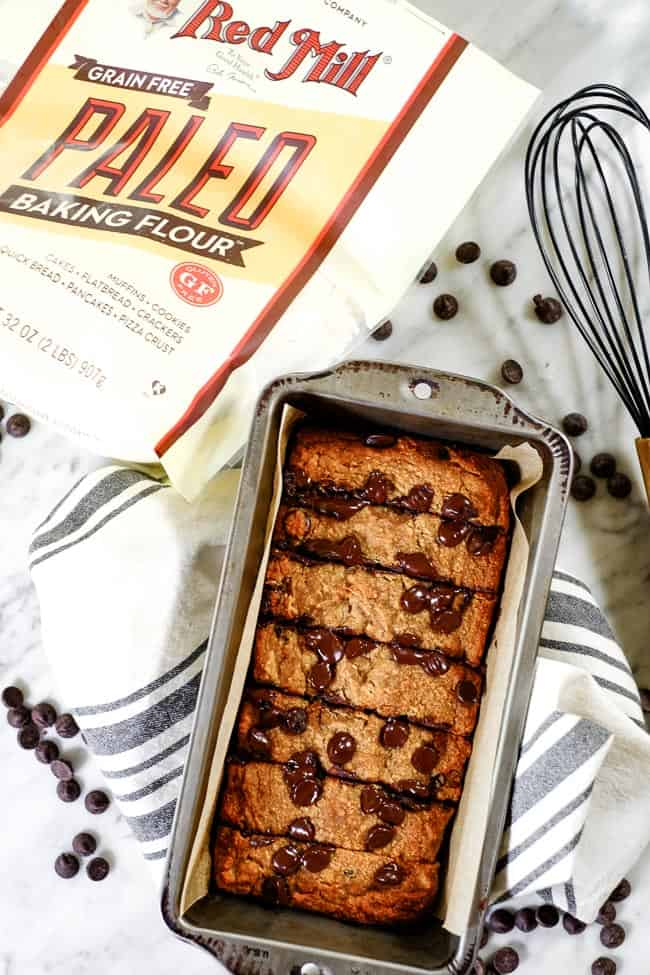 Paleo chocolate chip banana bread in bread pan on table with Bob's Red Mill Paleo Baking Flour, chocolate chips, a whisk and striped linen.