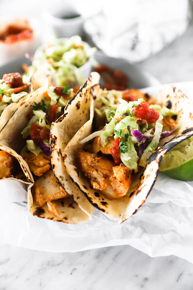 Vertical angled image close up image of fish tacos on a plate.