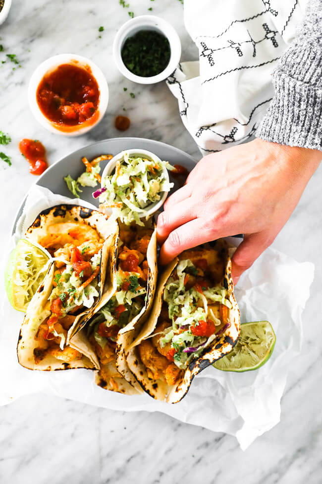 Overhead vertical image of hand coming in to pick up one taco from the plate of fish tacos.
