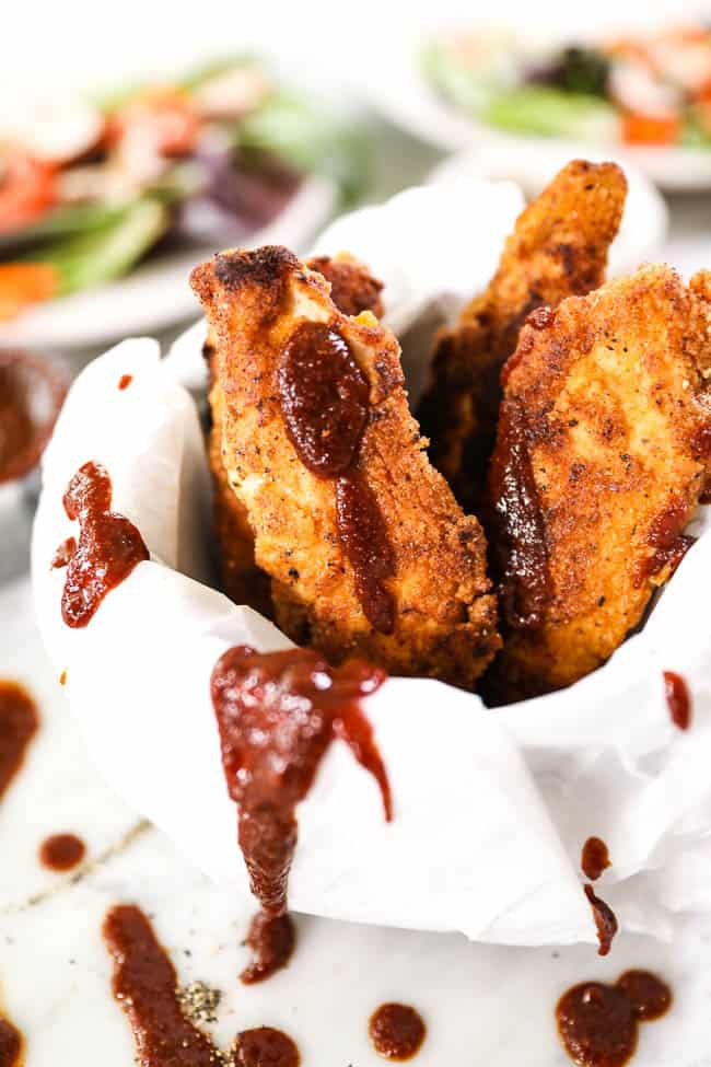 Paleo fried chicken like fries in a mug with parchment paper and drizzled BBQ sauce.