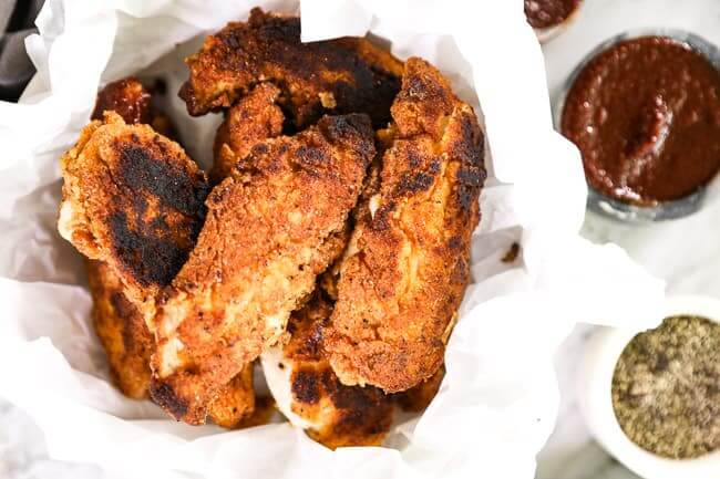 Paleo fried chicken layered in a bowl with parchment paper and BBQ sauce  and pepper on the side.