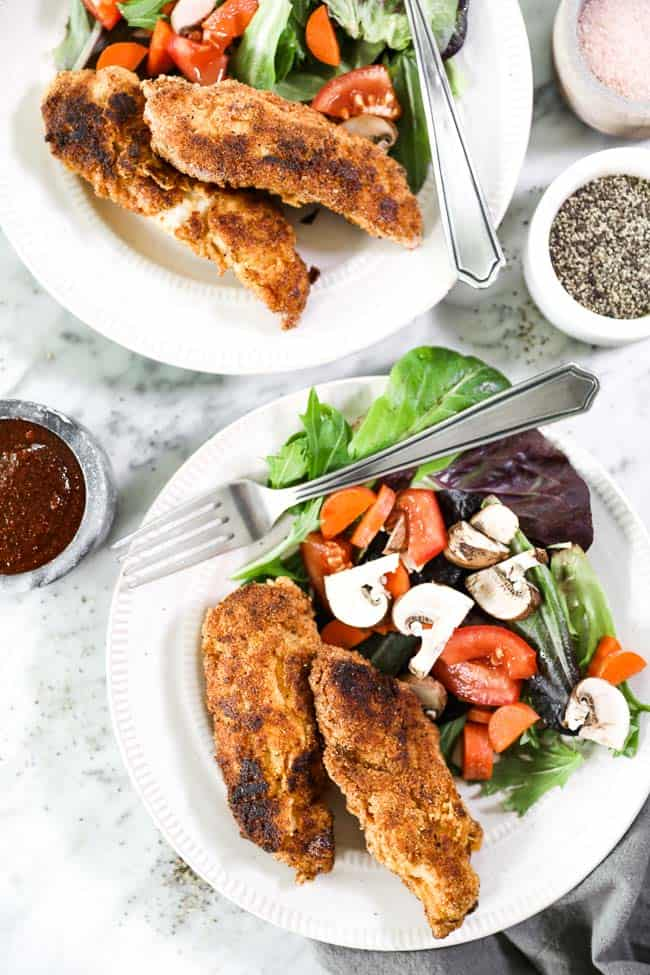 Paleo fried chicken served on two plates with side salads made with mixed greens, chopped carrots, tomatoes and mushrooms. BBQ dipping sauce on the side.