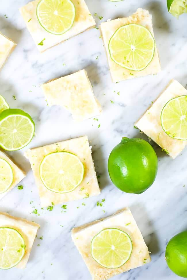 Paleo lime bars topped with lime zest and sliced lime.