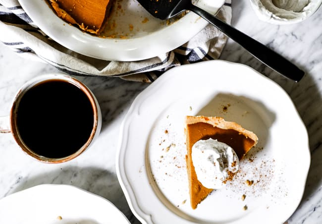 Slice of Paleo pumpkin pie on a plate with coconut whipped cream, extra cinnamon and a cup of coffee.