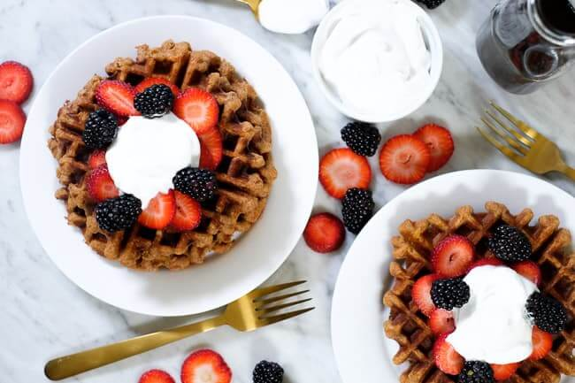 Paleo waffles topped with berries and coconut whipped cream.