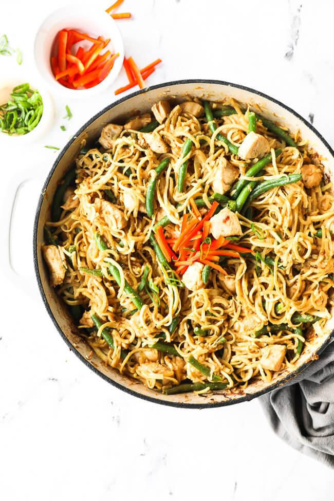 Overhead image of a large skillet with peanut butter chicken and noodles. Topped with chopped red pepper and green onions.