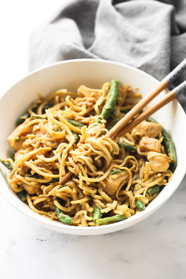 Angled image of peanut butter chicken and noodles in a bowl with some noodles spun around chopsticks.