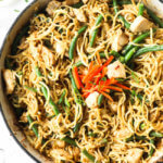Peanut butter chicken noodles in a pan with green beans, sliced red pepper and green onions