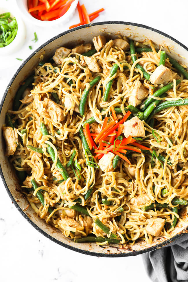 Large skillet filled with peanut butter chicken and spiralized sweet potato noodles.