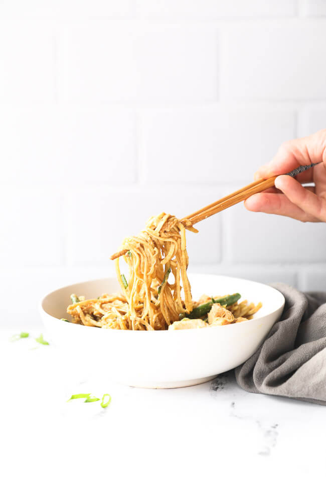 Straight on image of pulling some creamy peanut butter chicken noodles out of a bowl with chopsticks.