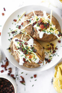 Overhead image of air fryer baked potatoes loaded with sour cream, cheese, bacon and chives