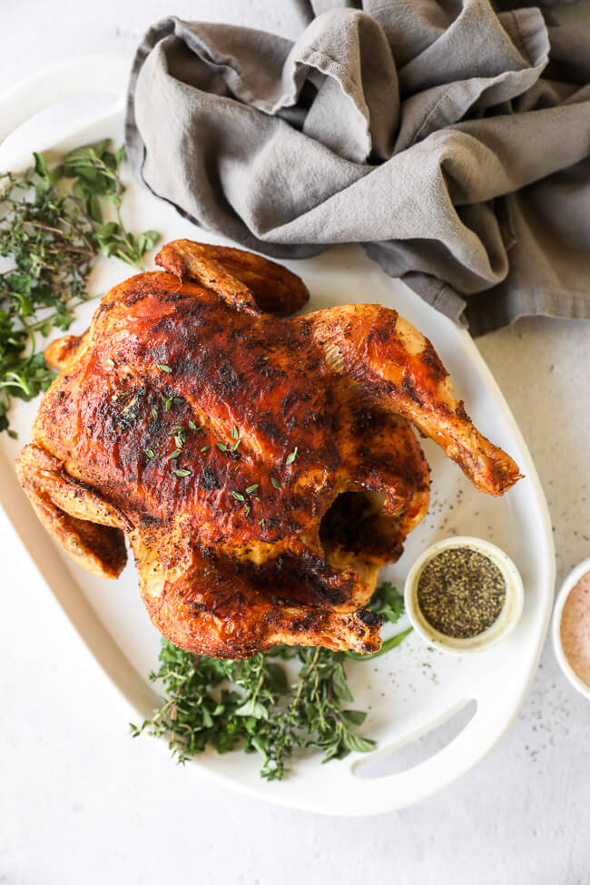 Whole air fryer roast chicken on a platter with fresh herbs around it
