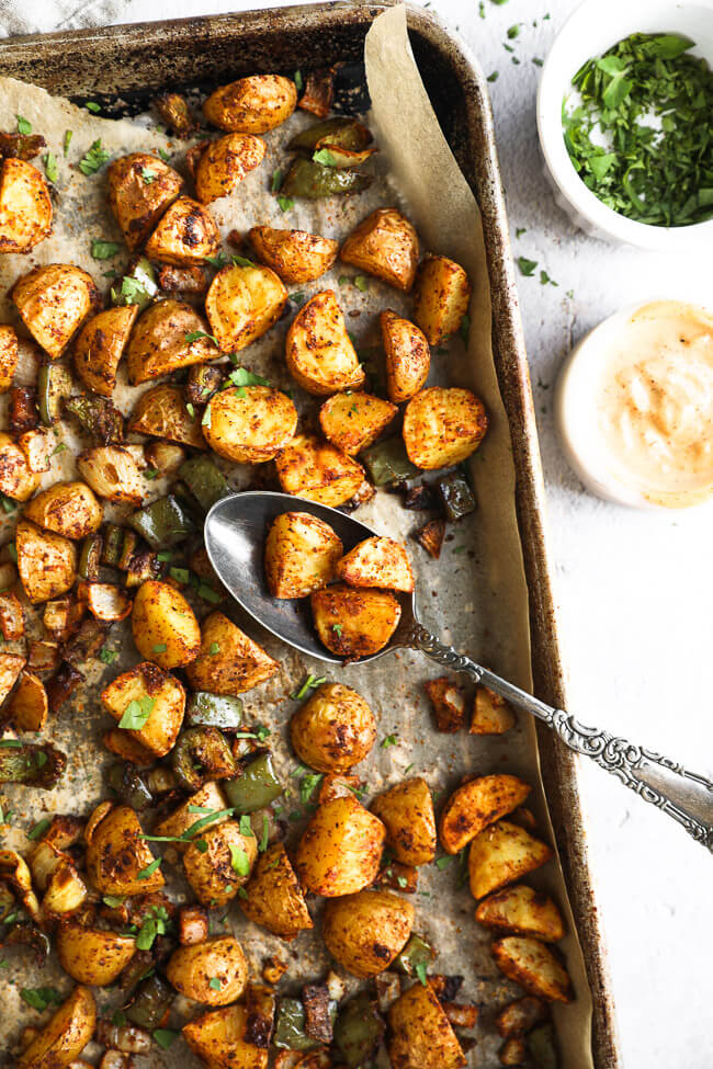 Roasted mexican potatoes on a sheet pan with spoonful of potatoes