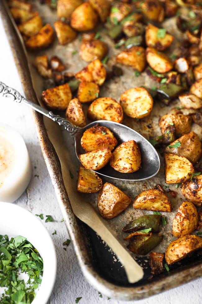 Roasted mexican potatoes on a sheet pan with spoonful of potatoes close up angle image