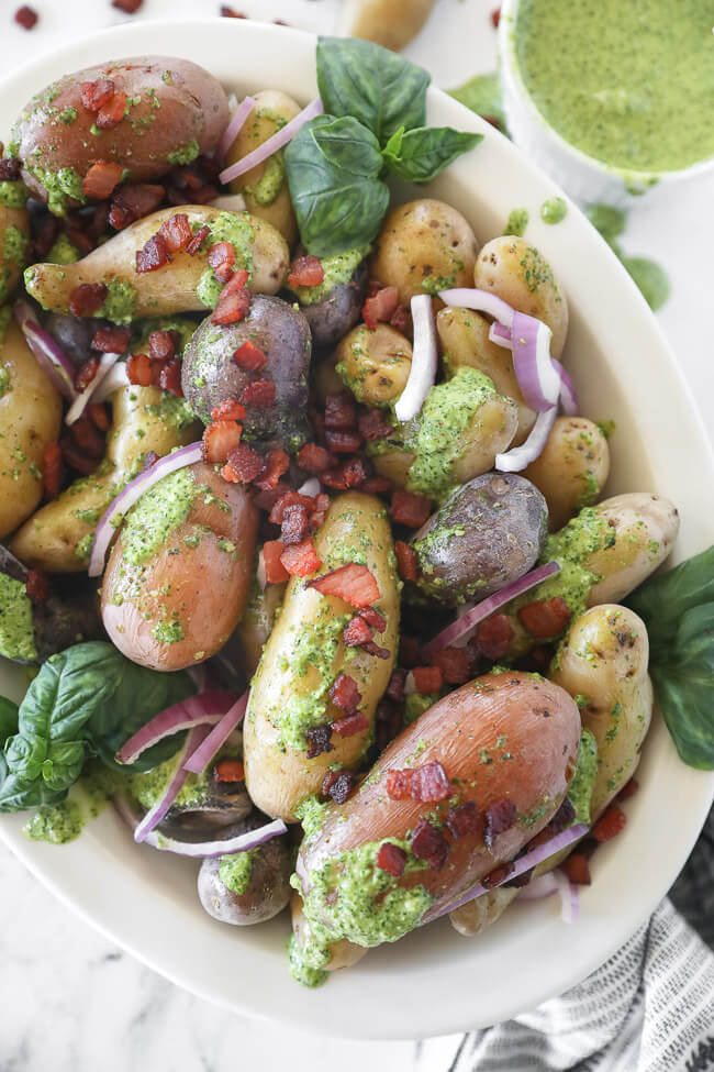 pesto potato salad in bowl with a bacon and red onion sprinkled on top close up vertical image