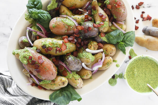 pesto potato salad in bowl with bacon sprinkled on top horizontal image