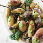 pesto potato salad in bowl with a spoon and bacon sprinkled on top vertical image