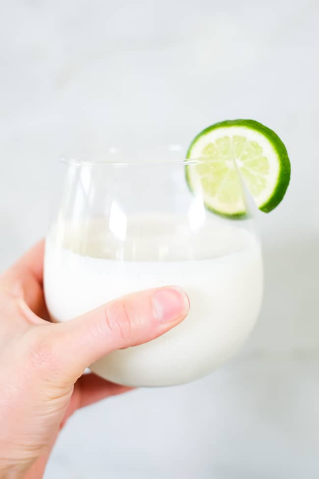Holding a glass of this paleo, dairy-free and refined sugar-free Two glasses of this paleo, dairy-free and refined sugar-free piña colada smoothie.