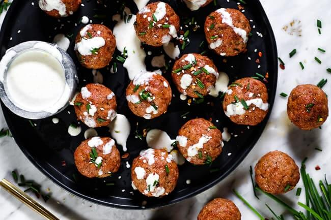 Pork meatballs on a plate with ranch dressing, chopped chives, red pepper chili flakes and sesame seeds.