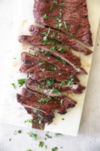 Quick and easy carne asada on a board cut into strips topped with salt and cilantro