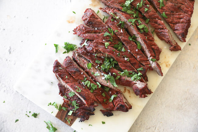 Quick and easy carne asada on a board cut into strips topped cilantro horizontal image